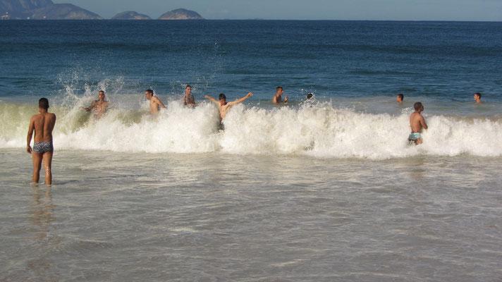 Eingeborene Jungmänner vernügen sich in den Wellen. (Strand von Copacabana)