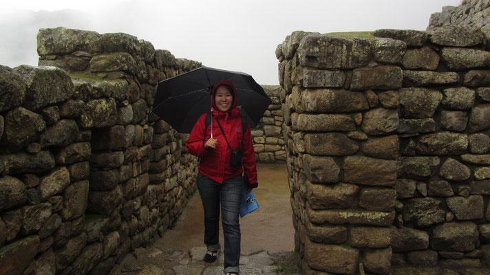 Mit Regenschirm bewaffnet in den Ruinen von Machu Picchu.
