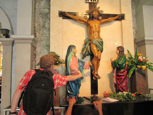 Begeisterter Tourist ahmt die gläubigen Eingeborenen nach und berührt eine Heiligenfigur. (Basilica Minore del Santo Nino)