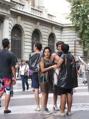 Junge Straßenartisten mit Müllsäcken.