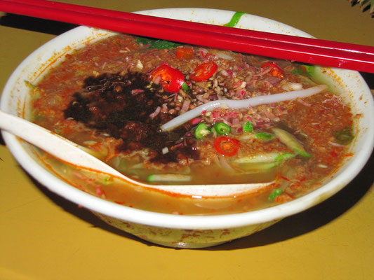 Penang Asam Laksa (Malay: Laksa Pulau Pinang), a dish of thick round rice noodles in a spicy and sour tamarind-based (or asam fruit-based) fish soup. The dish is garnished with mint, cucumber, onions, shreadded lettuce and pineapple.