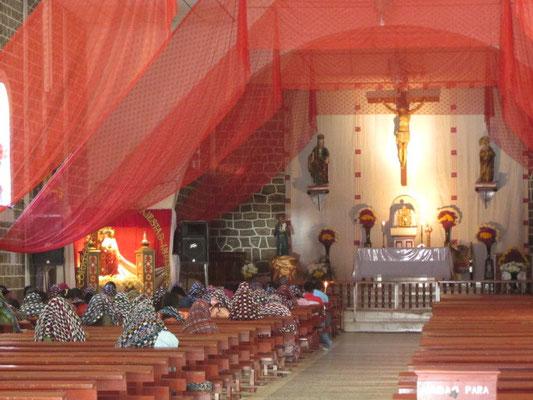 Einheimische Frauen bedecken ihre Köpfe mit Tüchern beim Gebet.