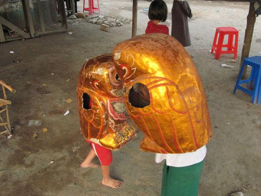 """""""Kampf der Giganten"""". Zwei Kinder haben sich Pappkostüme übergestülpt um sich zu bekriegen."""