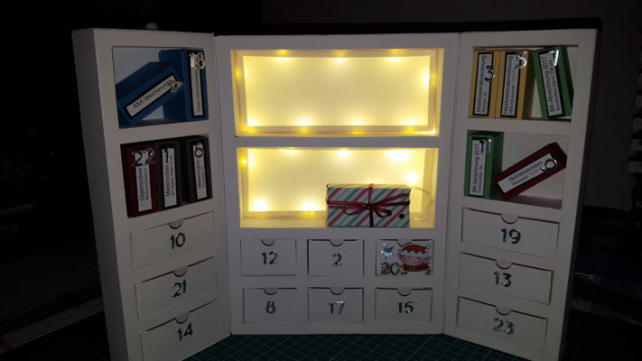 In der Mitte, im unteren Regal steht ein Geschenk. Hier habe ich das Batteriefach für die Beleuchtung versteckt. Die Batterien lassen sich jederzeit austauschen.