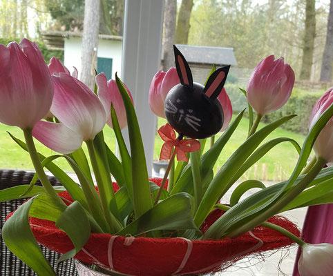 Färbe das Ei mit einem Edding oder Stempelfarbe schwarz. Stecke einen Schaschlikspieß in das Ei und klebe ihn fest.
