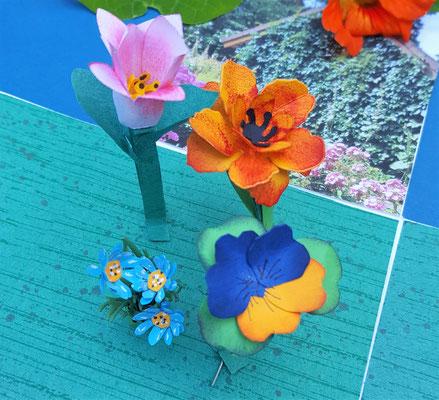 Die Blüten haben einen Draht im Stengel. Sie wurde vor dem Aufkleben durch den Boden gesteckt und auf der Rückseite befestigt. Erst dann wurde der Boden in die Box geklebt..