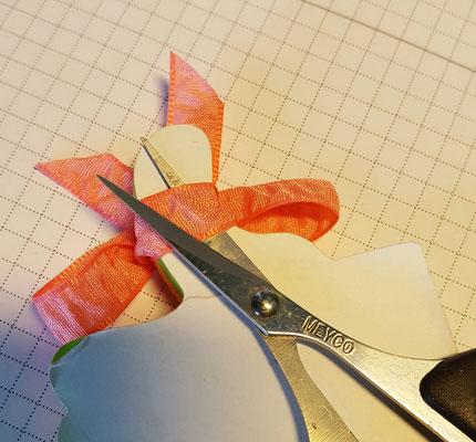 Binde eine Schleife um einen Stift oder schmalen Block. Binde eine Schleife. Schneide die Rückseite der Schleife auf und streiche Kleber drauf.