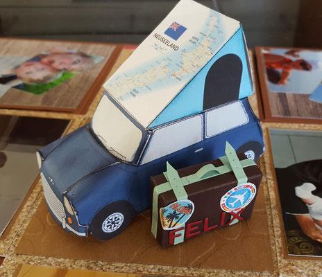 ein Mini mit Koffer und Neuseelandkarte und Zelt