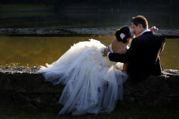 Küssen ; Braut ; Bräutigam ; Hochzeitskleid ; Anzug ; von hinten fotografiert