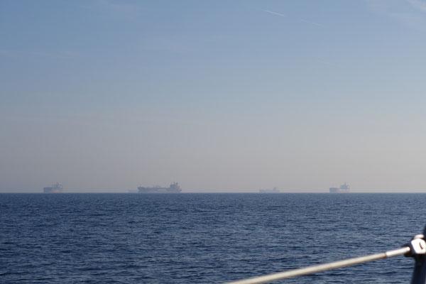 die ersten Containerschiffe tauchen aus dem Nebel auf