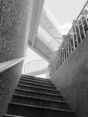 Un immeuble mystérieux, avec des escaliers et des coursives qui traversent une cour intérieure.