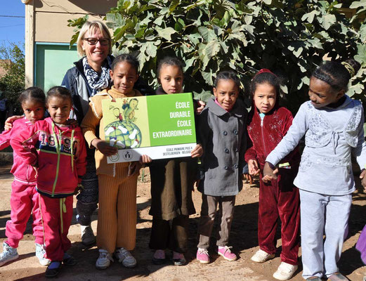 Annick met enkele leerlingen en het logo van de duurzame school