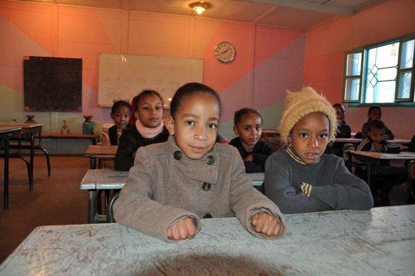De leerlingen goed ingeduffeld tegen de koude in de klaslokalen