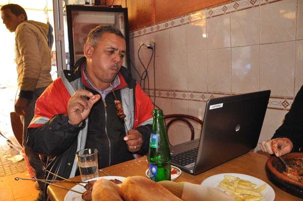 Onze chauffeur Hussein geniet van zijn eten terwijl hij de foto's bekijkt