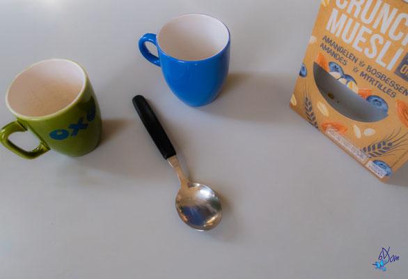 2 tasses et une cuillère, voici un visage en pleine discussion avec une boîte de muesli