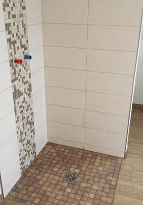 Barrierefreie Badsanierung mit bodengleicher Dusche und Ablaufrinne in der Mitte der Dusche