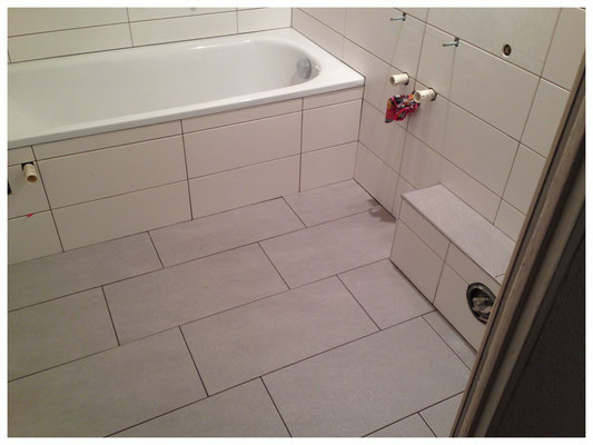 Bad nach der Sanierung mit Wanne und neuen Wand- und Bodenfliesen