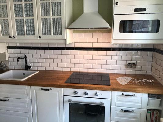 Küchenfliesenspiegel im weißen Metrogedesign - abgesetzt mit einer schwarzen Bordüre