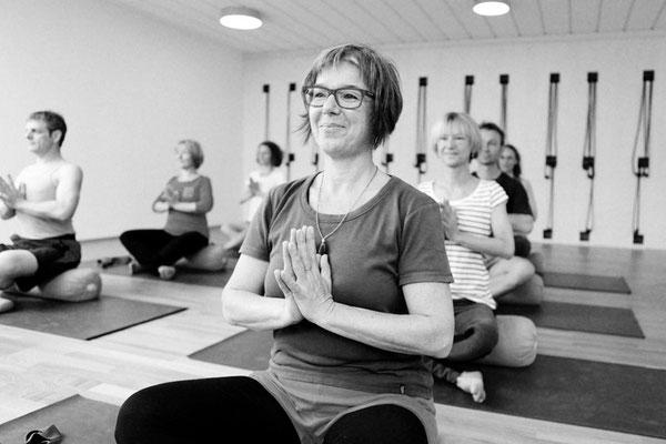 Übende in Atmanjalimudra, Sitzen zu Beginn einer Yogastunde