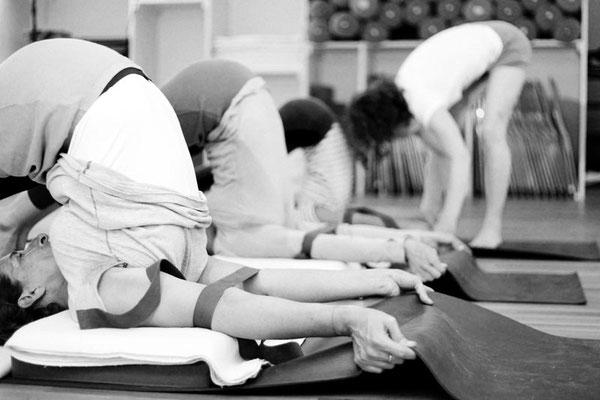Praxis von Asana, Halasana, Übende im Pflug, kraftvolles Greifen der Matte um die Schultern zu Positionieren, Korrektur