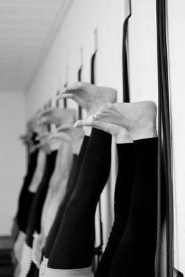 Praxis von Asana, Sirsasana, Beine von Übenden im Kopfstand an der Wand