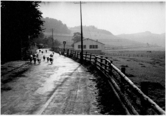 """Bild Thorsten Conze: Altenilpe nach 61 (im Hintergrund ist ein Trecker zu sehen),  Blick auf die Schützenhalle, rechts Straßenschild """"Schule"""""""