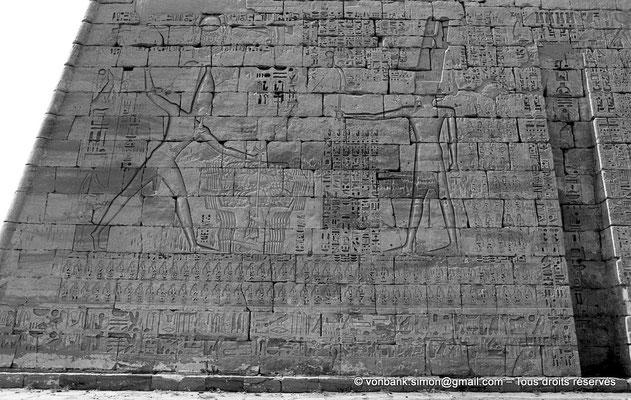 [NB086-1981-47] Medinet Habou : Devant Amon, Pharaon tient par les cheveux des captifs qu'il s'apprête à abattre avec une massue (Détail du Premier pylône du grand temple de Ramsès III)