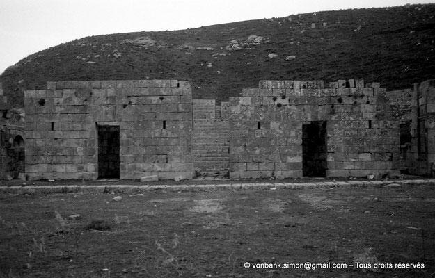 [NB034-1978-53] Khemissa (Thubursicu Numidarum) : Esplanade du théâtre avec sa façade partielle et sa porte centrale donnant accès à la scène. En arrière-plan, les gradins adossés sur la colline