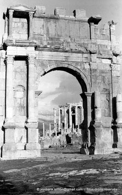 [NB037-1978-21] Djemila (Cuicul) : Arc de Caracalla - Façade Ouest - En arrière-plan, le Temple Septimien