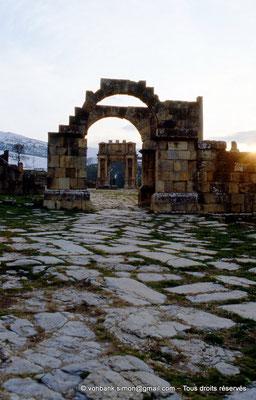 [013-1984-05] Djemila (Cuicul) : Place des Sévères (Nouveau forum) - Arc de l'Est - En arrière-plan, l'arc de Caracalla