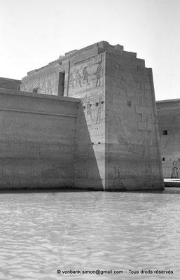 [NB076-1973-51] Philae : Temple d'Isis (parties supérieures de la façade Ouest) - Pronaos, Pylône 2, toit du Mammisi (au ras de l'eau), Pylône 1