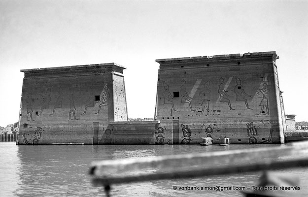 [NB076-1973-73] Philae : Temple d'Isis - Porte d'Evergete (linteau au ras de l'eau) - Façade du Pylône 1