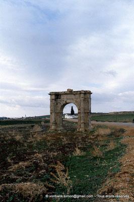 [034-1983-24] El [034-1983-24] Krib (Musti) : Arc dit de Gordien III, avec à sa gauche les ruines du mausolée des Julii - En arrière-plan, le marabout de Sidi Abd Rabou