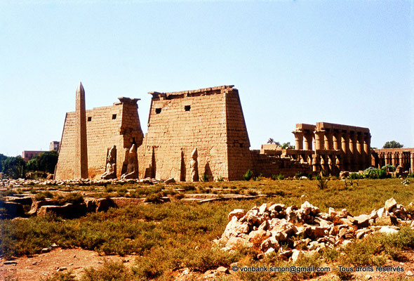 [080-1973-39] Louxor - Temple d'Amon-Rê : Avant-cour, obélisque, statues, pylône et grande cour (Ramsès II) puis colonnade processionnelle d'accueil (Aménophis III)
