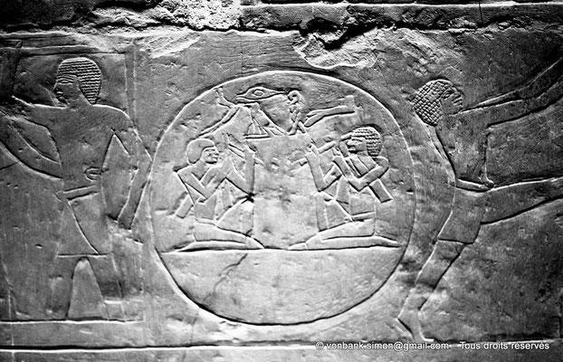 [NB080-1973-09] Saqqara - Mastaba de Mererouka : Inscrits dans un cercle : deux hommes agenouillés et portant des équerres et des ciseaux à pierre préparent (?) une cuve pour recueillir le vin pressé (Chambre A12, mur Nord)