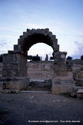 """[034-1983-30] Aïn Tounga (Thignica) : Arc de triomphe - En arrière-plan, le temple dit """"de Mercure"""""""