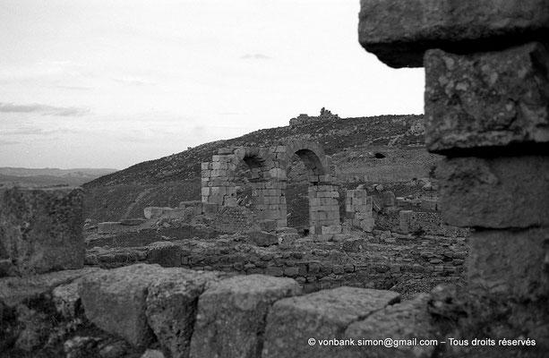[NB034-1978-45] Khemissa (Thubursicu Numidarum) : L'arc à trois baies avec en arrière-plan, les ruines du Ksar el Kebir (Fort byzantin)