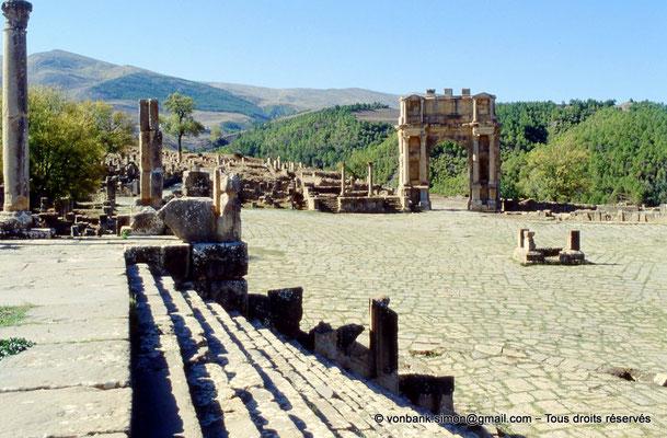 [001-1983-35] Djemila (Cuicul) : Place des Sévères (Nouveau forum) - Colonnes de la maison de la mosaïque d'Hylas, podium du petit temple et arc de Caracalla