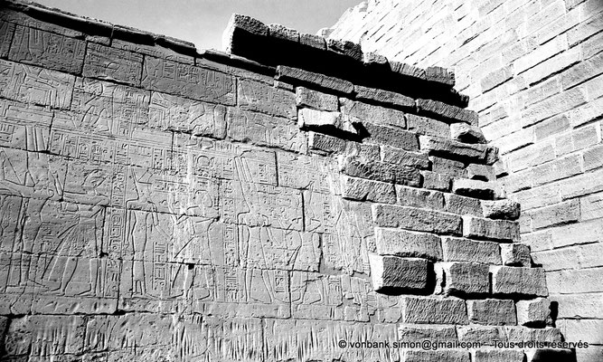 [NB077-1973-50] Karnak - Temple de Séthi II : Paroi extérieure Nord (Vue partielle) - Sethi II oint Amon-Rê représenté ithyphallique avec les attributs de Min - Sethi II offre du vin à Amonet - Sethi II offre 2 vases à Amon-Rê
