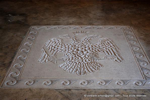[NU900x-2013-0133] Crète - Chrysoskalítissa : Au sol de l'église, Aigle bicéphale couronnée tenant dans ses serres un glaive (sceptre) et un globe terrestre (surmonté d'une croix) (drapeau de l'Église orthodoxe)