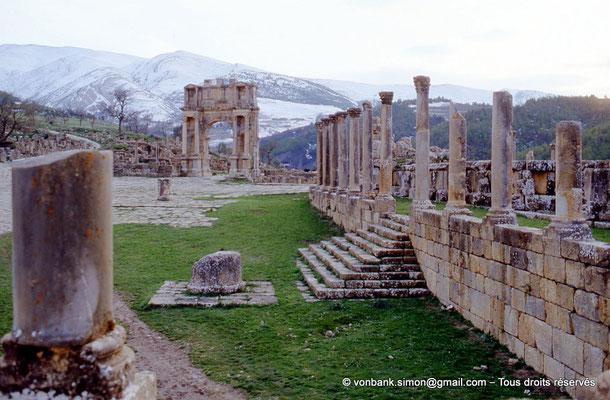 [013-1984-06] Djemila (Cuicul) : Place des Sévères (Nouveau forum) - Arc de Caracalla et escalier d'accès au portique Nord (en arrière-plan, les montagnes enneigées)