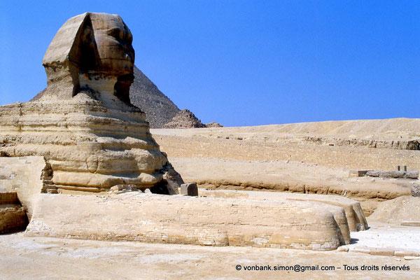 [068-1981-07] Gizeh - Grand sphinx : Le Sphinx érodé avec entre ses pattes (le haut de) la stèle de Thoutmosis IV - En arrière-plan, la pyramide de Khéops et l'une de ses trois pyramides des Reines