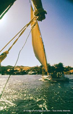 [091-1973-39] Assouan : Mausolée de l'Aga Khan III : Traversée du Nil en felouque pour se rendre sur la rive opposée - En arrière-plan, sur la droite, on peut apercevoir le mausolée