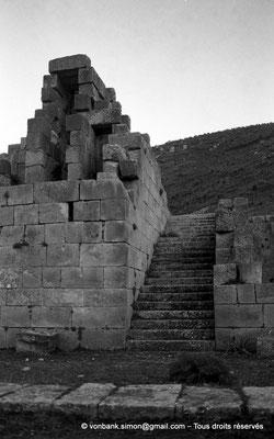 [NB034-1978-55] Khemissa (Thubursicu Numidarum) : Vu depuis l'esplanade du théâtre, sur la droite de la façade, escalier permettant l'accès à un palier desservant la loge d'honneur et la partie supérieure des gradins de la cavea
