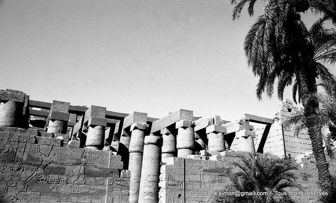 [NB075-1973-30] Karnak - Salle hypostyle : Porte dans la paroi extérieure Nord - Mur des campagnes de Séthi Ier - En arrière-plan, colonnes à chapiteaux papyriformes fermés