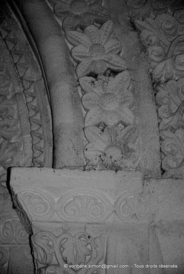 [NU904-2015-0081] 17 - Sainte-Gemme - Avant-nef : Fleurs des voussures de la porte donnant accès à la nef (détail de la partie droite)