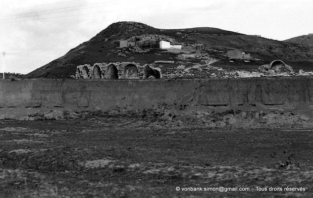 [NB044-1978-17] Chemtou (Simitthu) : Théâtre - Vu depuis le lit de l'oued Melah - En arrière-plan, l'abside du marché