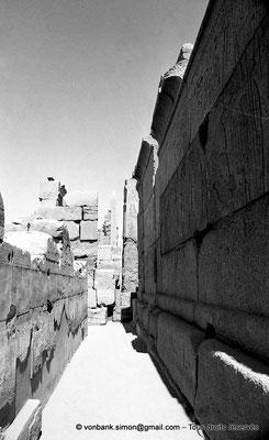 [NB078-1973-56] Karnak - Ipet-Sout : Passage le long de la paroi Sud de la chapelle de Philippe Arrhidée - En arrière-plan, obélisque de Thoutmôsis Ier