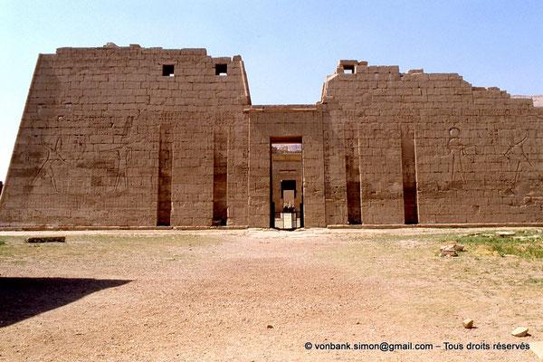 [069-1981-37] Medinet Habou : Premier pylône du grand temple de Ramsès III (Pharaon savoure sa victoire sous la protection d'Amon-Rê et de Rê-Horakhty)