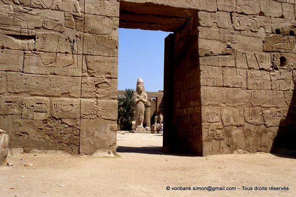[068-1981-15] Karnak - Grande cour : Statue de Ramsès II vue depuis la cour du temple-reposoir de Ramsès III